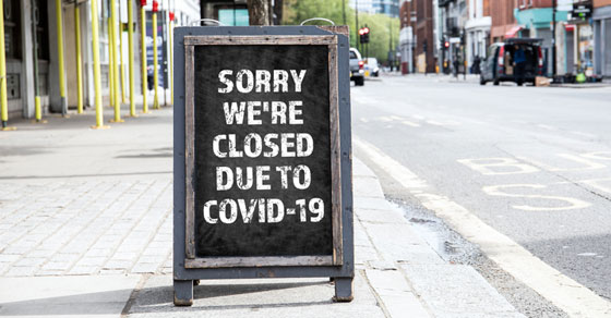 Sidewalk sign saying Sorry We're Closed Due to COVID-19