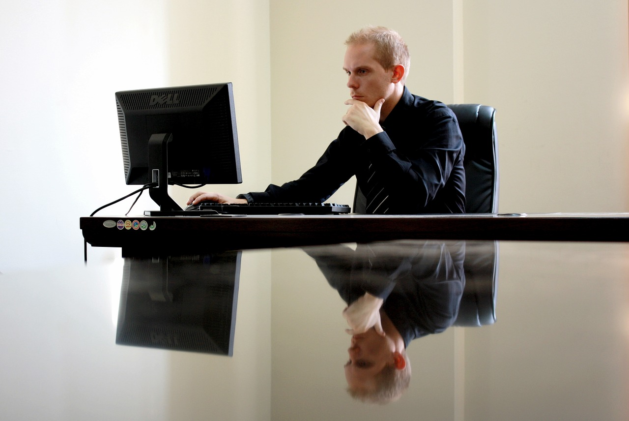 Business man sitting at a computer thinking about 2020 taxes