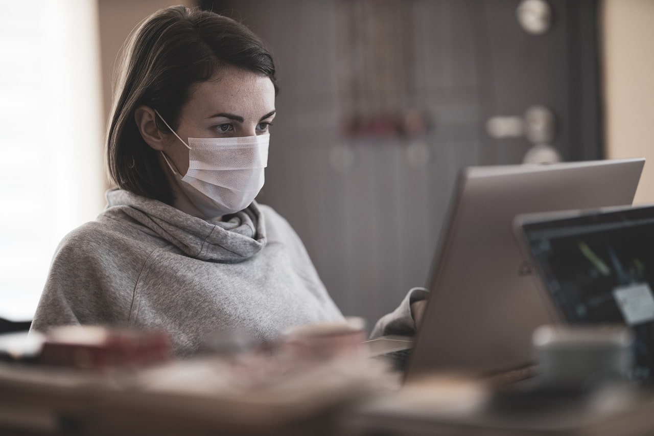 woman wearing a mask at a computer doing small business bookkeeping