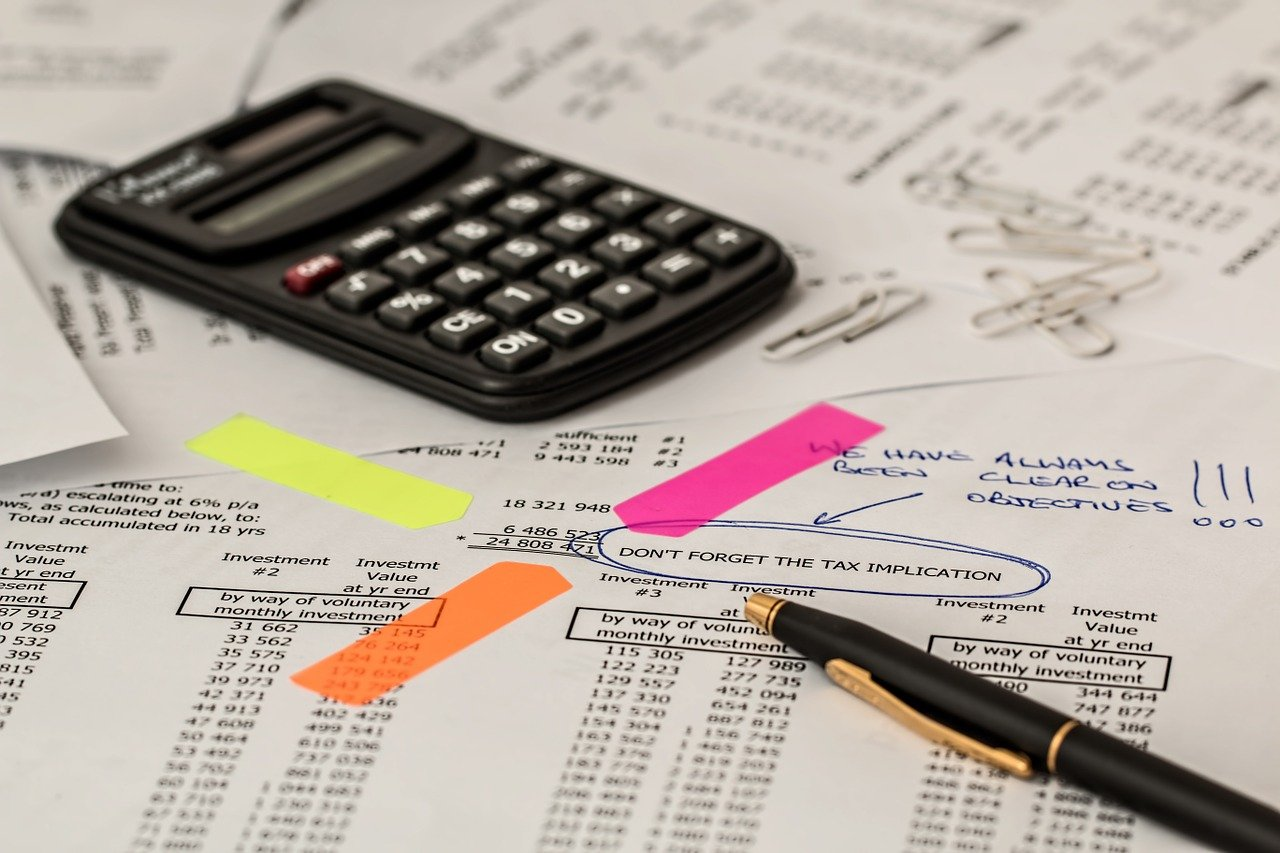 Tax documents, calculator, pen and post-it tab markers