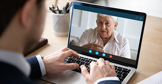 man looking at a laptop screen while video chatting with an older family member